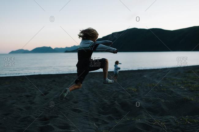 Boy doing running jump on beach at dusk