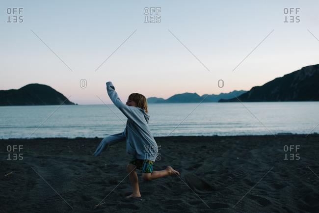 Boy running on a beach at dusk