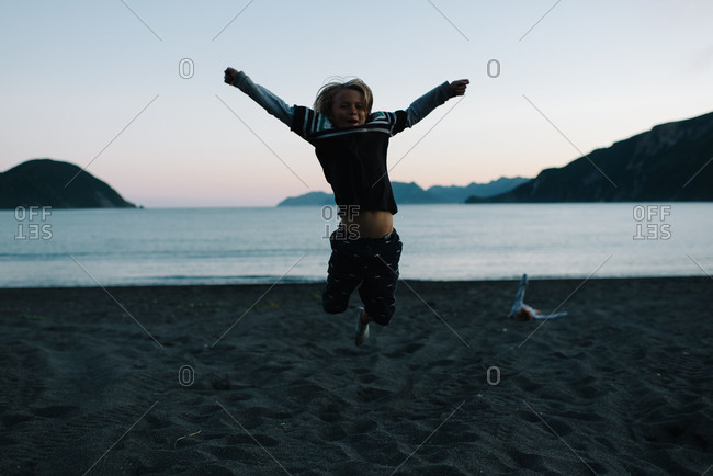 Boy leaping into the air on beach at dusk