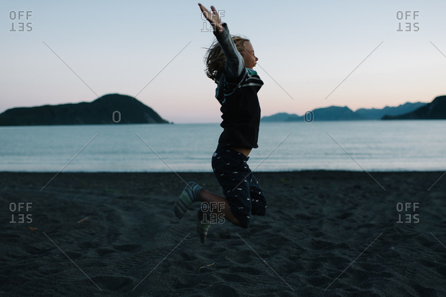 Boy jumping into the air on beach at dusk