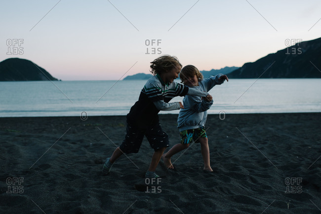 Two boys playing together on beach at dusk