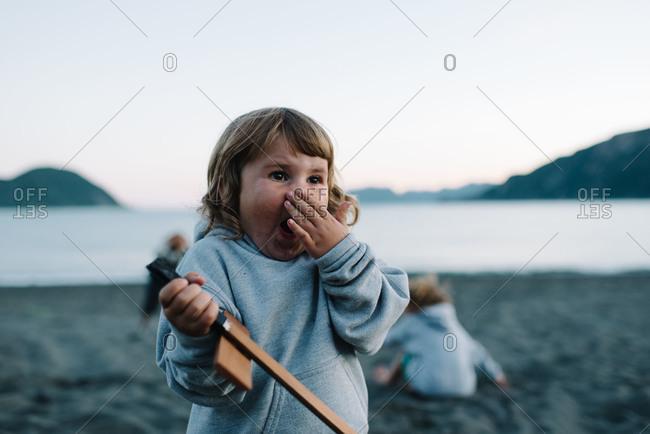 Little girl yawning on beach at dusk