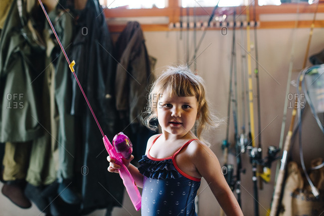 Girl in a garage holding a fishing pole