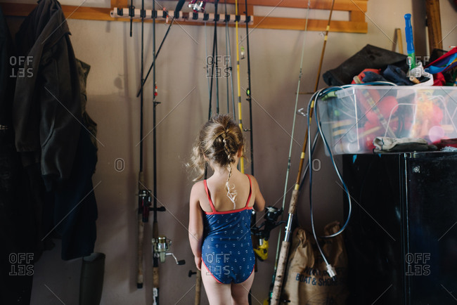 Little girl in swimsuit looking at fishing poles