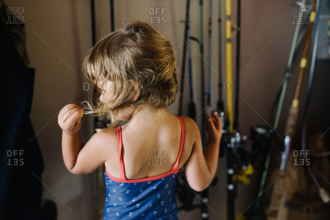 Girl in garage in swimsuit looking at braid
