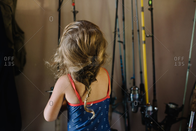 Girl in a garage in swimsuit looking at fishing poles