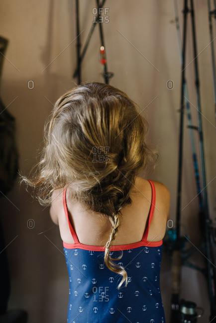 Girl looking at fishing poles hanging in garage