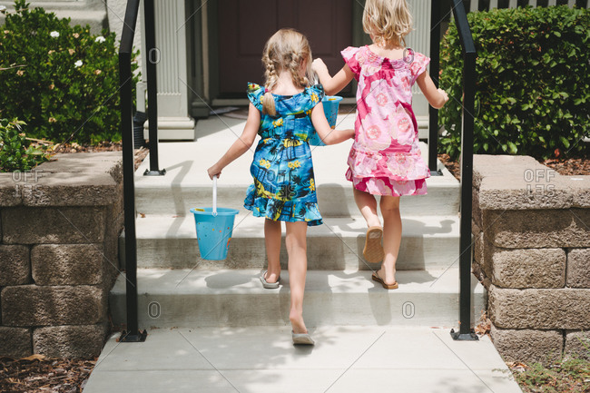 Two young girls in tropical print dresses walking upstairs with beach pails