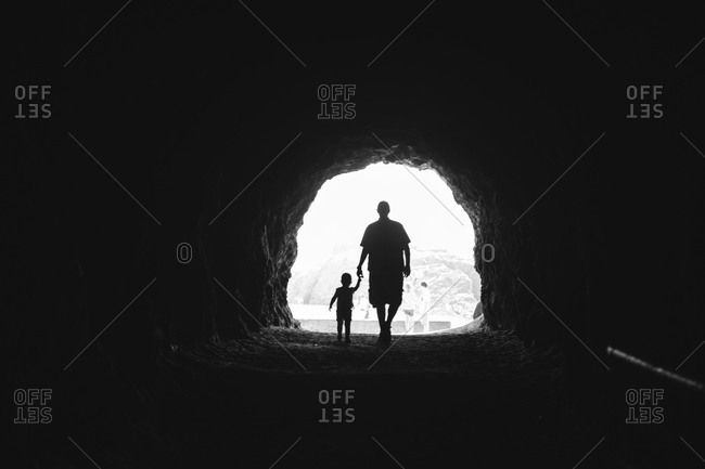 Father and child walking through a tunnel