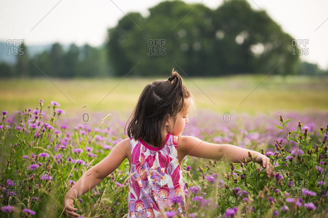 Young girl walking through field of purple flowers