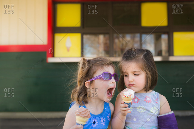 Girl watches unhappily as her sister tries to taste her ice cream cone