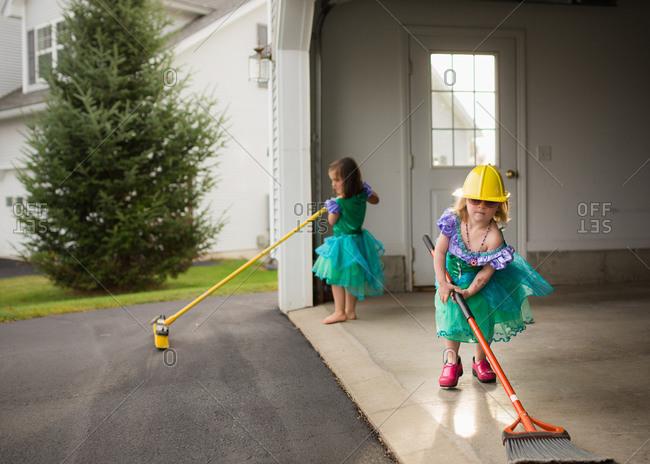 Two girls in princess dresses sweep their garage floor