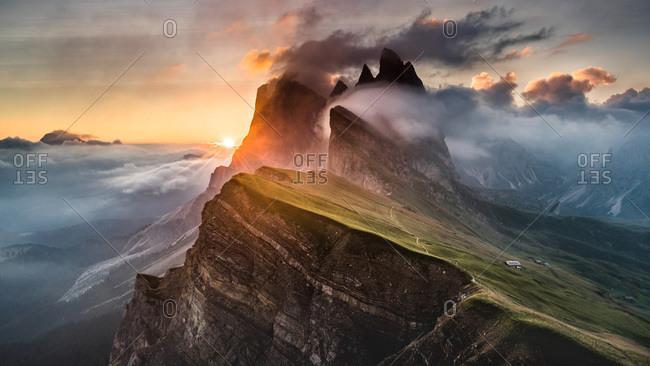 Fog covered cliffs in Italian alps at sunrise