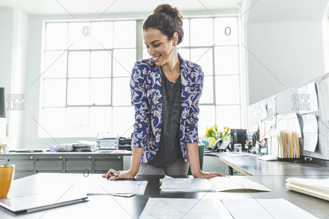 Woman looking over paperwork at her desk