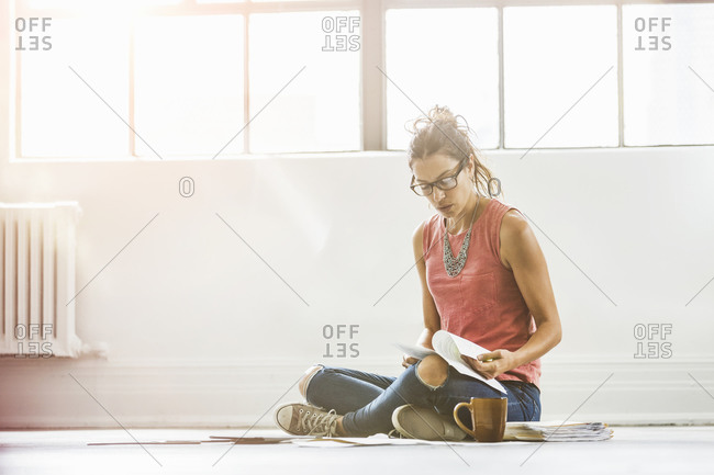 Woman sitting on the floor looking at paperwork