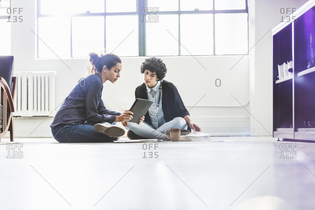 Women sitting on floor and with smart tablet in an office