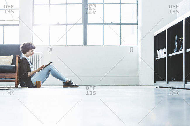 Woman sitting on floor and with smart tablet in an office