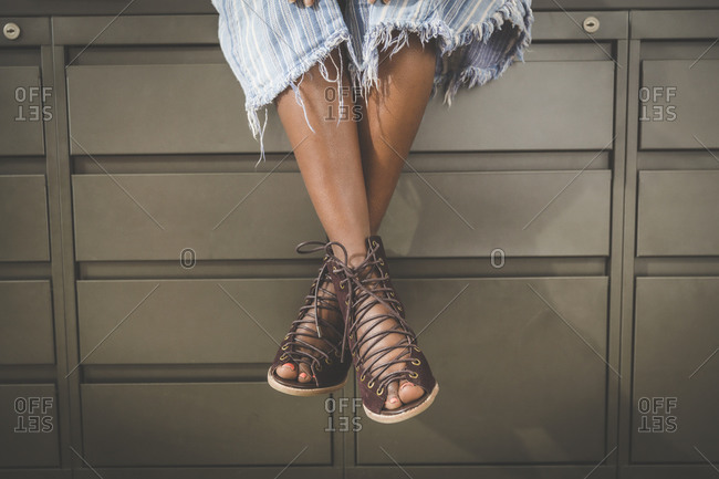 Fashionable worker sitting on file cabinets
