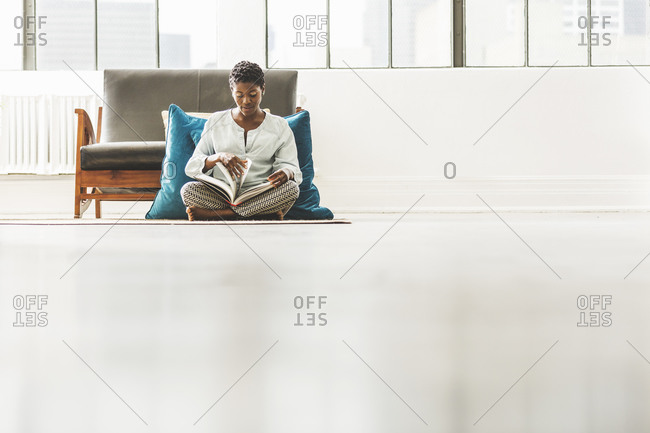 Woman sitting on the floor reading