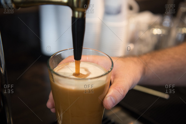 Glass of nitro coffee being filled from a tap