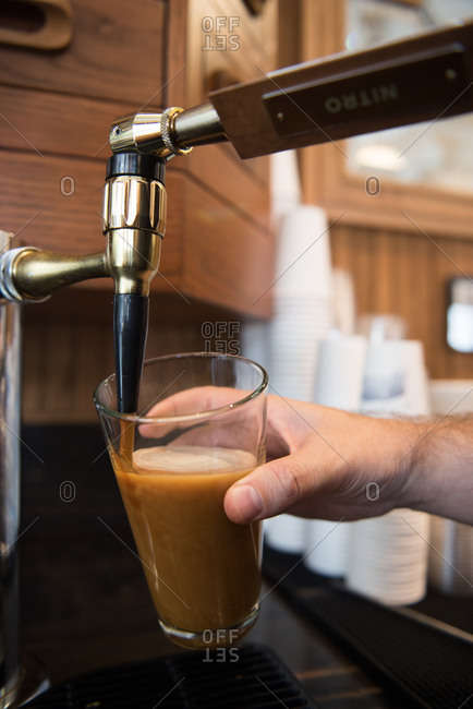 Nitrogen infused coffee being poured from a tap