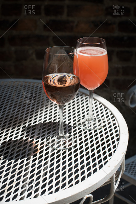 Pink drinks in wine glasses on a patio table