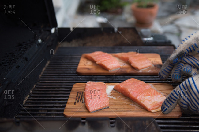 Hands placing planks of salmon on a grill