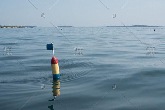 Buoy with flag floating in calm water