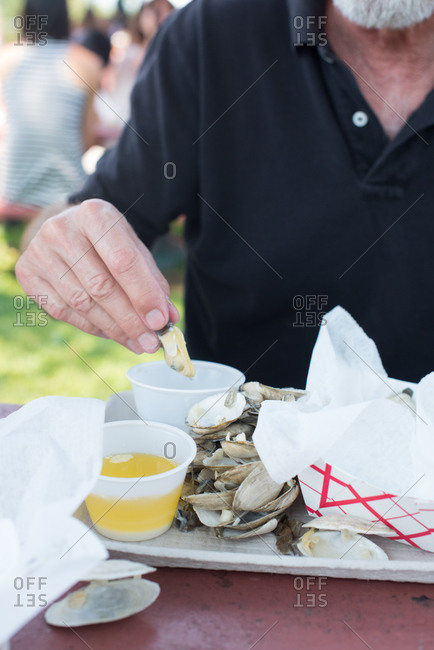 Man eating steamed clams at a picnic table