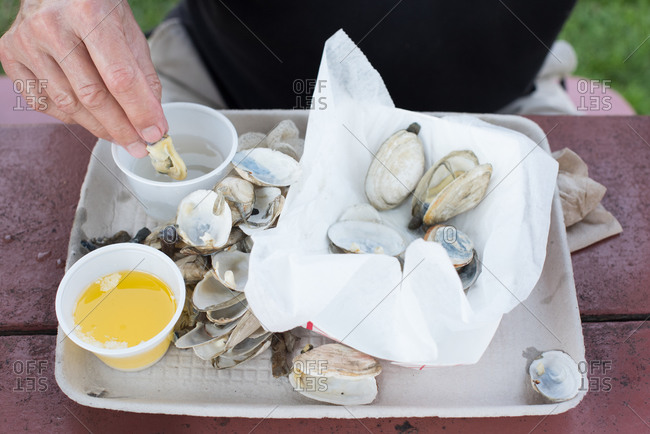Man dipping steamed clams in broth before eating