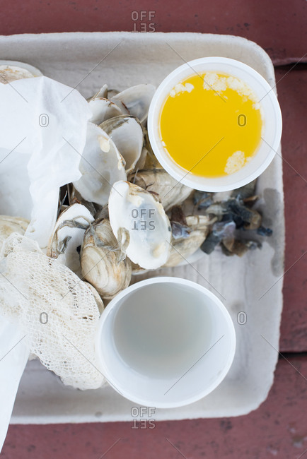 Empty steamed clam shells with butter and broth for dipping