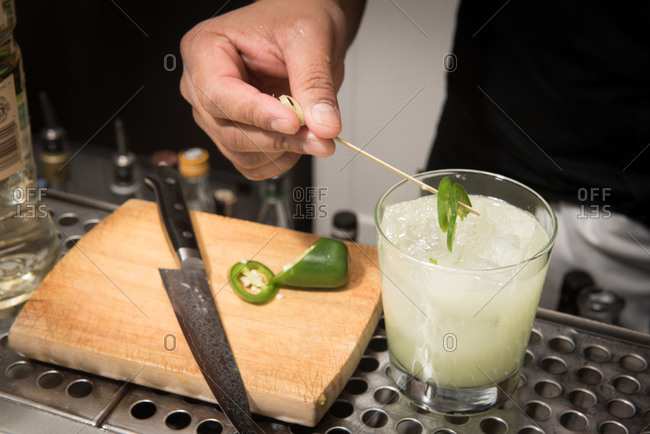 Bartender garnishing a cocktail with jalapeno