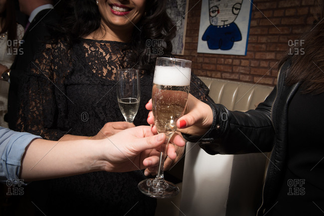 Server handing a woman a champagne glass at a party