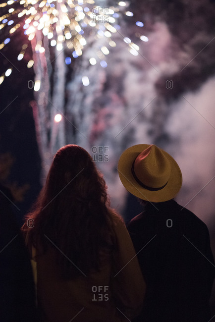 Young couple watching fireworks at night