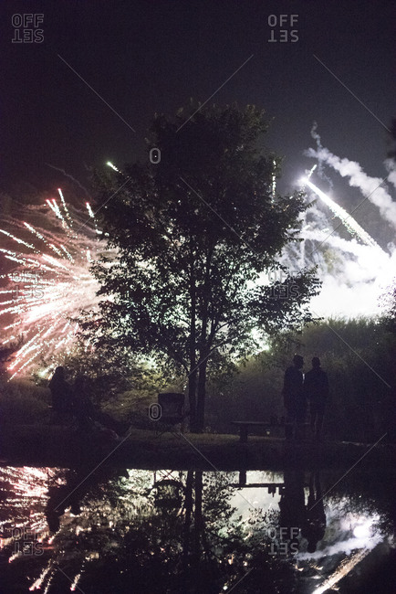 People watching fireworks from a lake shore