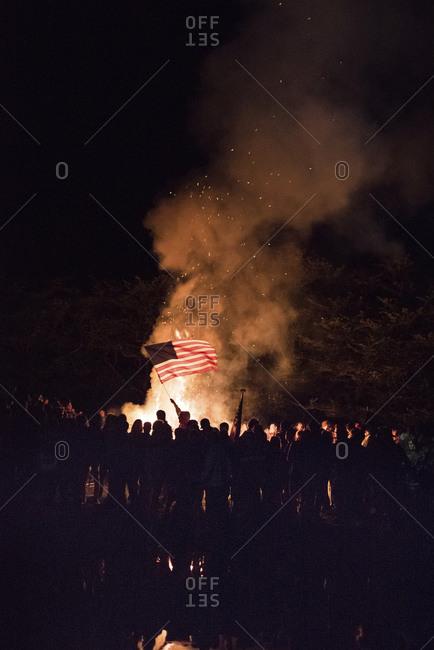 People waving an American flag at a bonfire
