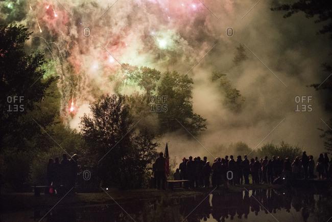 People watching colorful fireworks through smoke