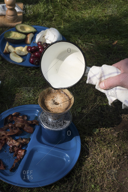 Person pouring water into a drip coffee maker at a campsite