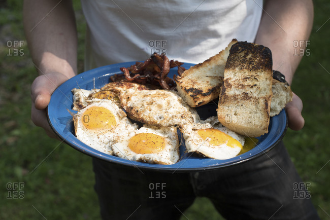 Man holding a plate of breakfast food