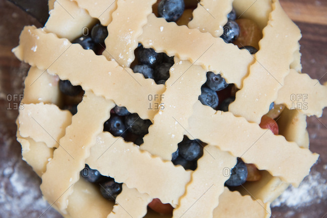 Lattice crust pieces over an uncooked blueberry and plum pie