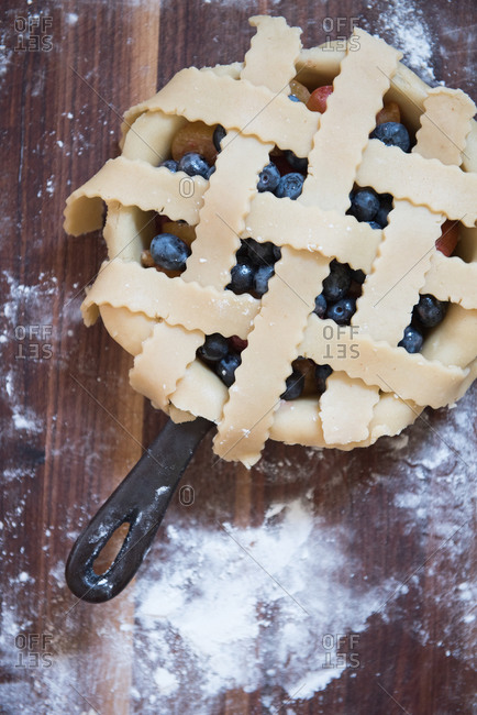 Uncooked blueberry and plum pie with lattice crust