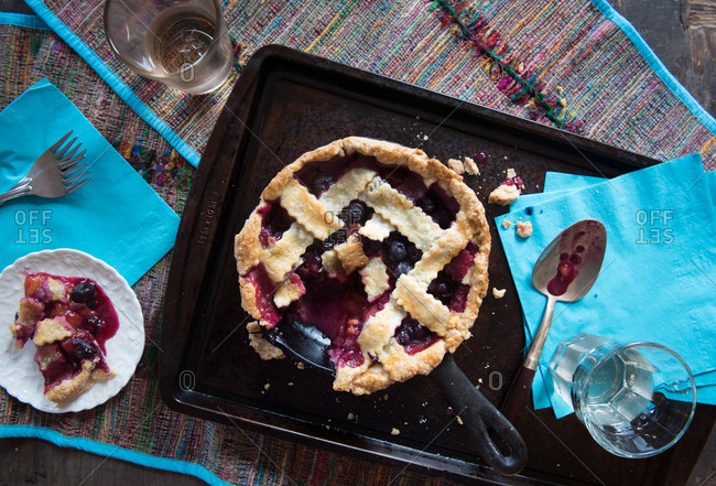Blueberry and plum pie with a piece on a plate
