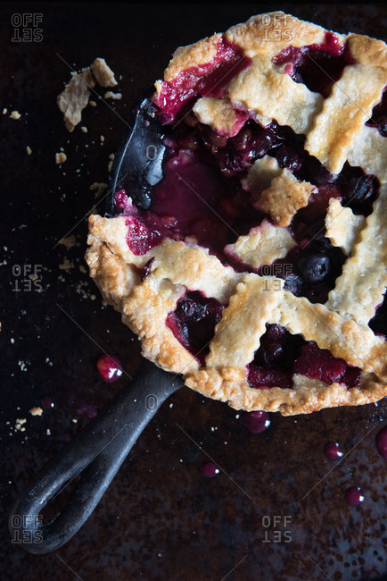 Blueberry and plum pie with a piece cut out