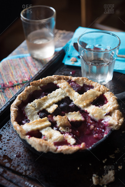 Blueberry and plum pie on a baking sheet with a piece removed