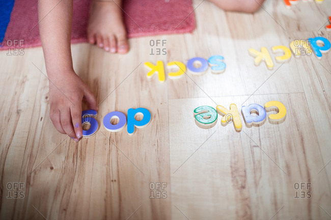 A child uses block letters to spell words on the floor