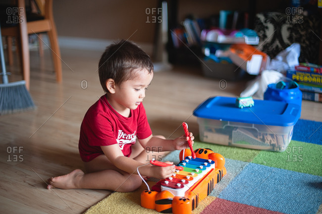 Boy playing a toy xylophone