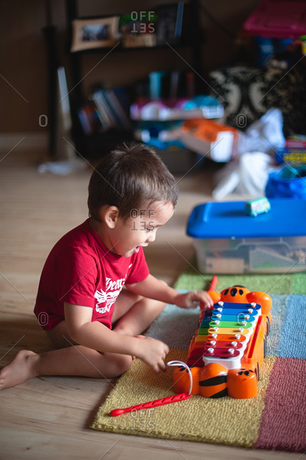 Boy playing with a toy xylophone