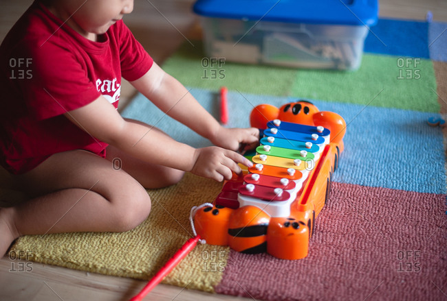 Toy xylophone being played by a little boy
