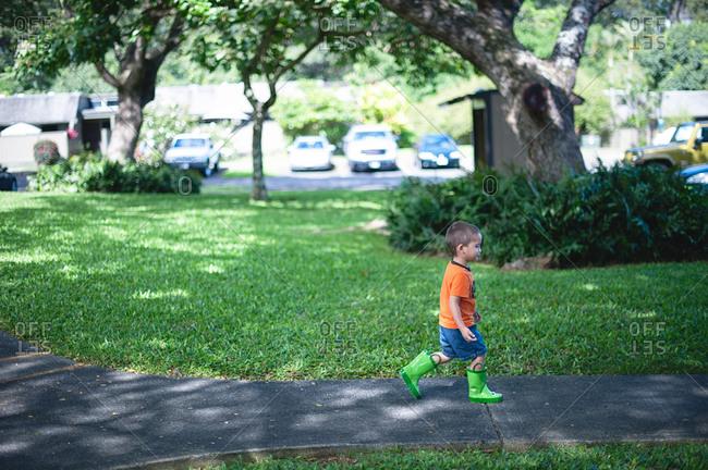 Little boy walking in rain boots