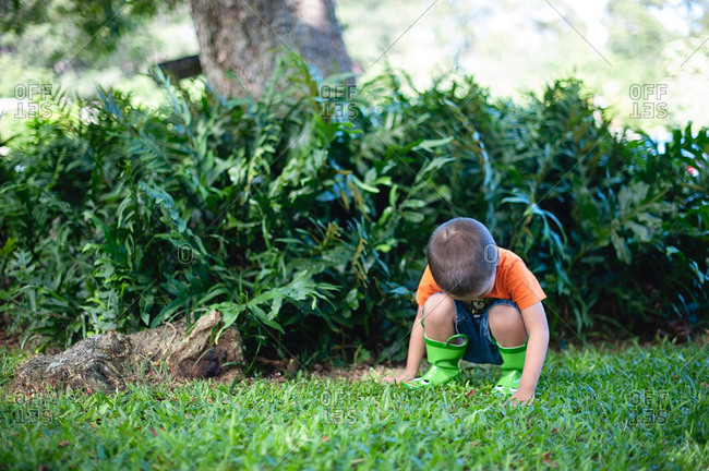 Boy wearing rain boots playing in grass